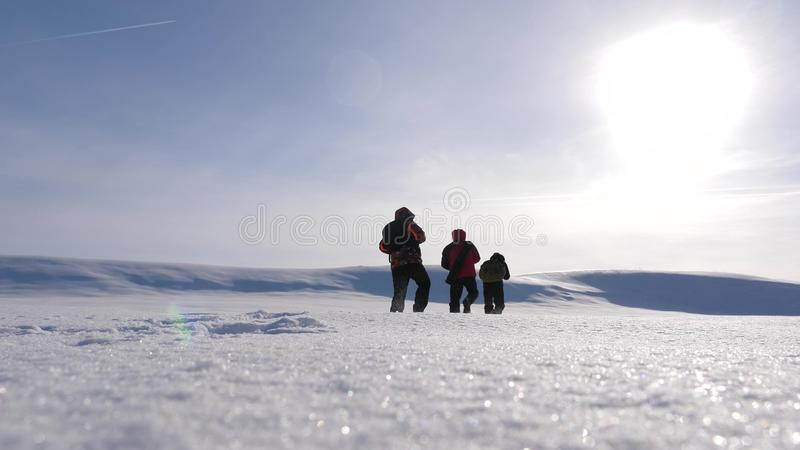 Team work and victory. three alpinist tourists follow each other in the snowy desert. team of business people go to. Team work and victory. three alpinist stock image