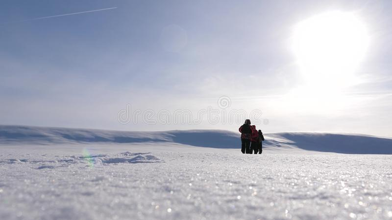 Team work and victory. three alpinist tourists follow each other in the snowy desert. team of business people go to. Team work and victory. three alpinist stock images