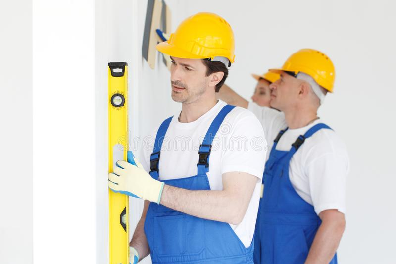 Team of workers align wall. At new house royalty free stock photos