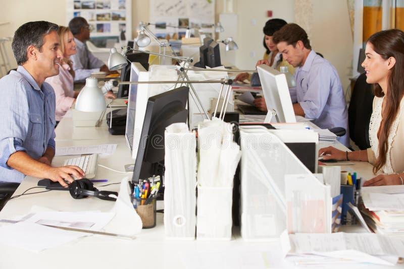 Team Working At Desks In upptaget kontor arkivbilder