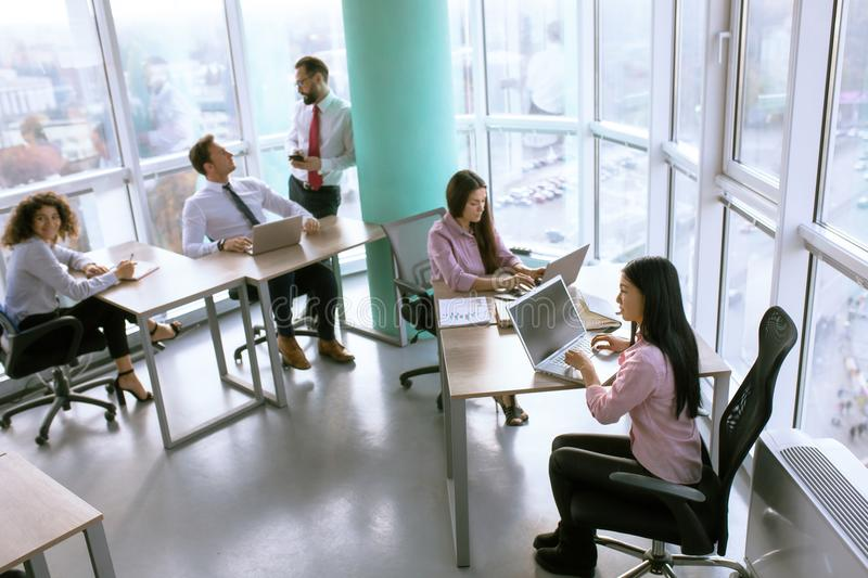 Team working process on international project. Team members in comfortable office discussing project milestone. Business concept stock photos