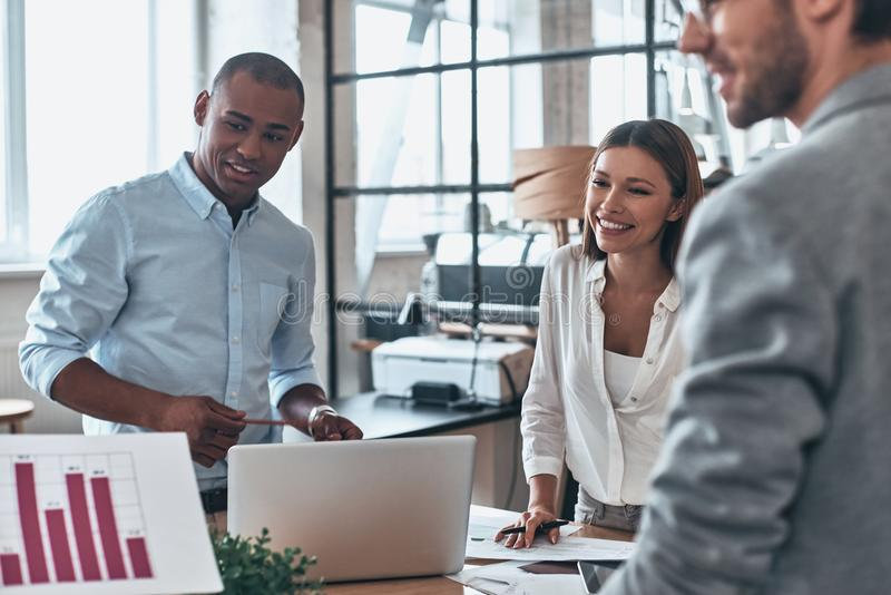 Team working together. Group of young modern people in smart casual wear discussing business while standing in the creative office royalty free stock image