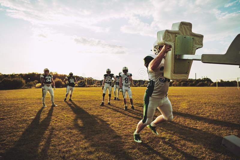 Football players doing tackling drills together on a sports fiel royalty free stock photography
