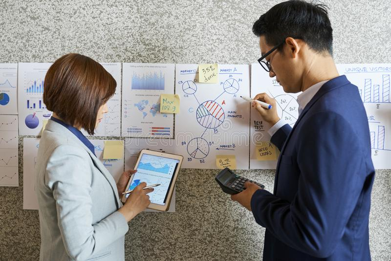 Financial analysts working with documents. Team young Asian financial analysts working on its data in financial documents stock photo