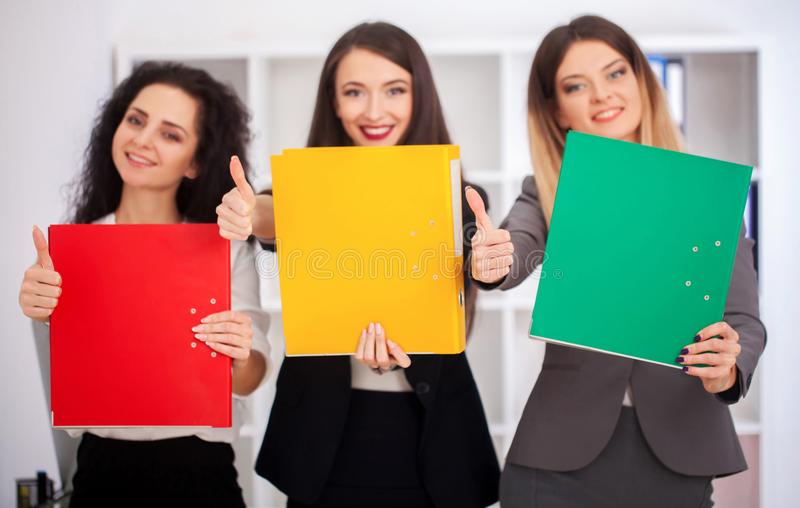 A team of young beautiful workers with colorful folders in their. Hands looking at the camera in the office. Brainstorm royalty free stock photo
