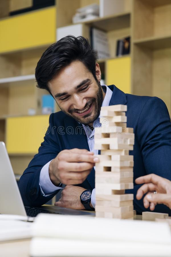 Team of young business people build a wooden construction stock image