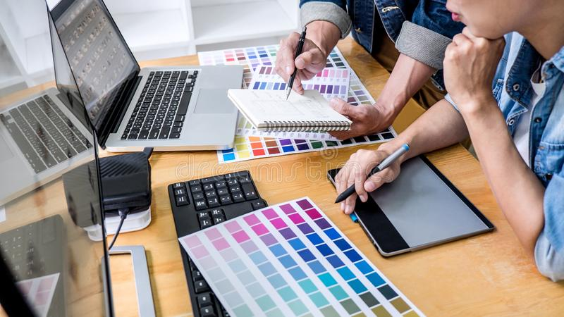 Team of young colleagues creative graphic designer working on color selection and drawing on graphics tablet at workplace, Color stock photo