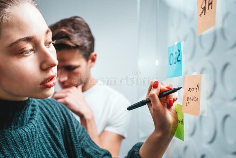 Team of young coworkers meeting and brainstorming new business ideas uses post it notes to share idea. Colleagues working on project plan together in office stock image