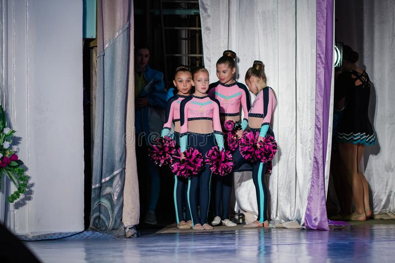 Team of young girls - athletes are preparing for the show, many young cheerleaders are standing on stage behind the curtain, sport royalty free stock photos