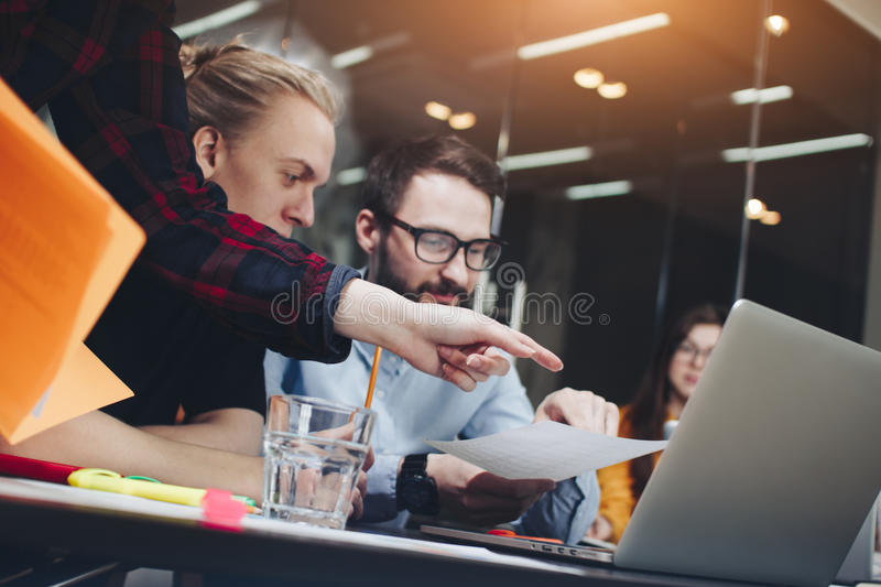 Team of young managers works in a modern office at a wooden table, modern gadgets, laptop and paper. Coworking stock images