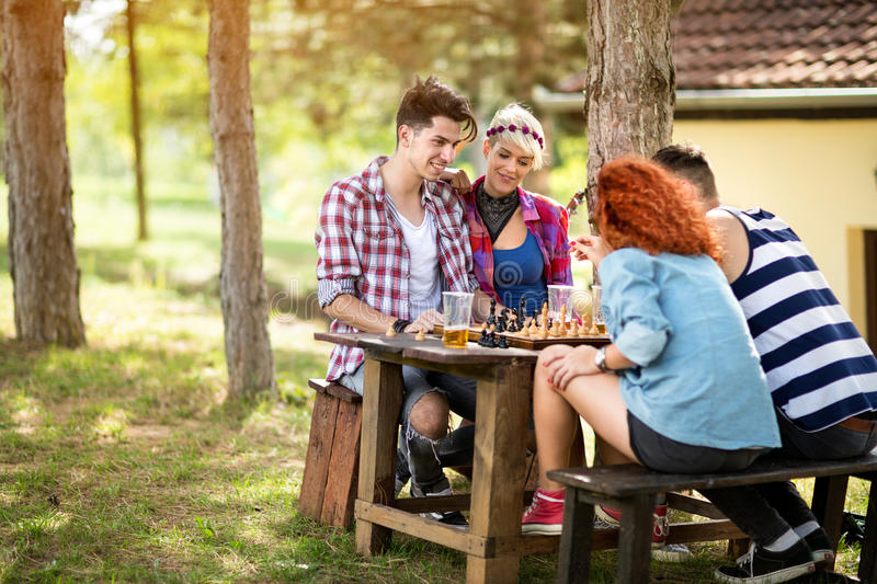 Team of young people play chess. Team of young people with pleasure play chess on picnic stock images