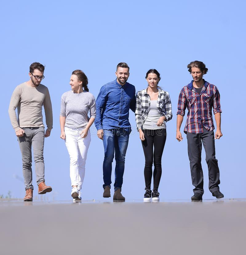Team of young people walking along the road.outdoors. Closeup .a team of young people walking along the road.outdoors.photo with copy space stock photo