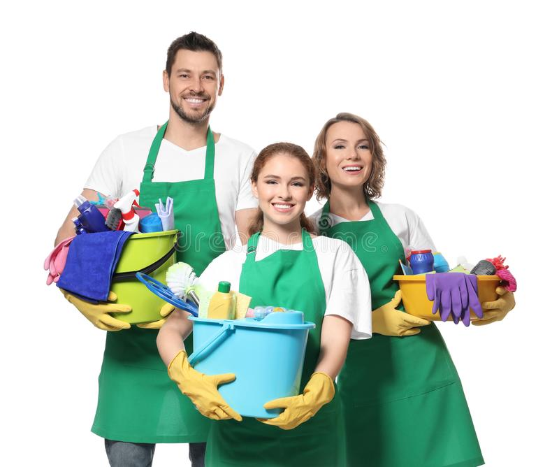 Team of young professionals with cleaning supplies. Isolated on white royalty free stock images
