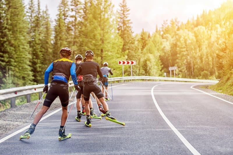 Teambiotlonists gaan op rolskis stock foto's