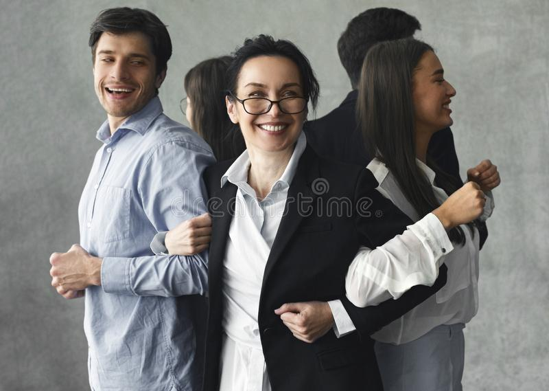 Business team standing in vicious circle and smiling stock images