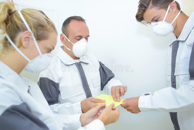 Teamdecorateurs die schuurpapier voelen die maskers dragen royalty-vrije stock foto's