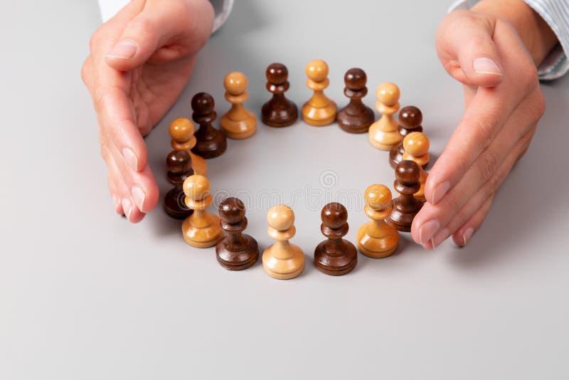 Teamkonzept, Führungskonzept Frauenhände rund um die im Kreis stehenden Schachfiguren stockfotografie