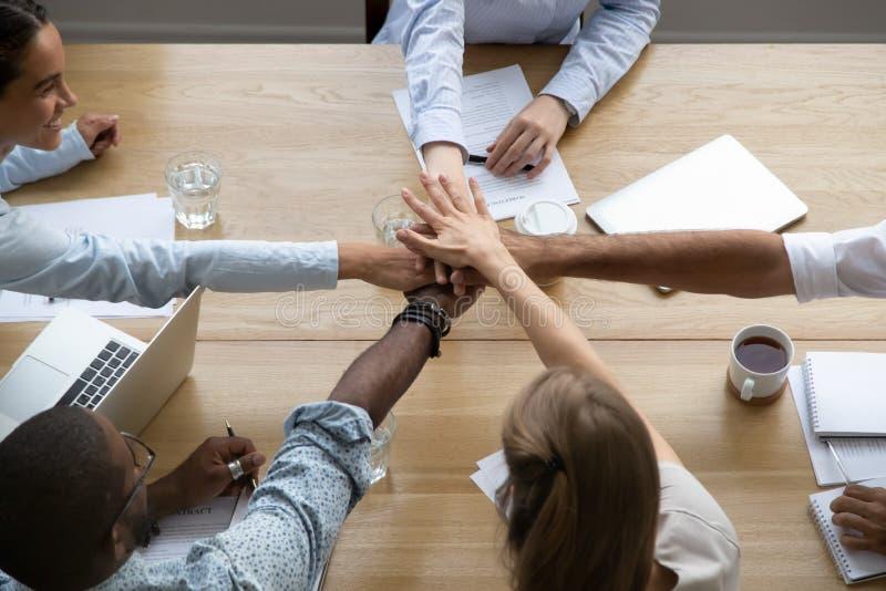 Teammensen die handen samen over lijst belast met het teambuilding stapelen stock foto's