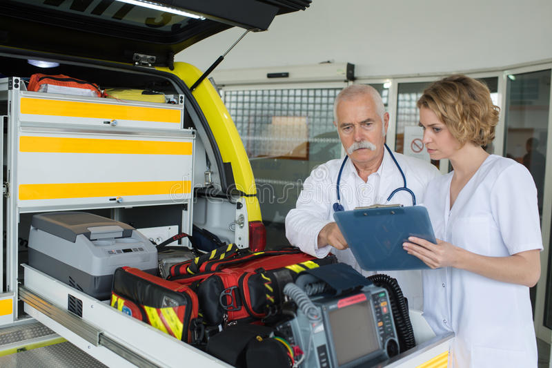 Teamparamedici die toestel in ziekenwagen controleren royalty-vrije stock fotografie