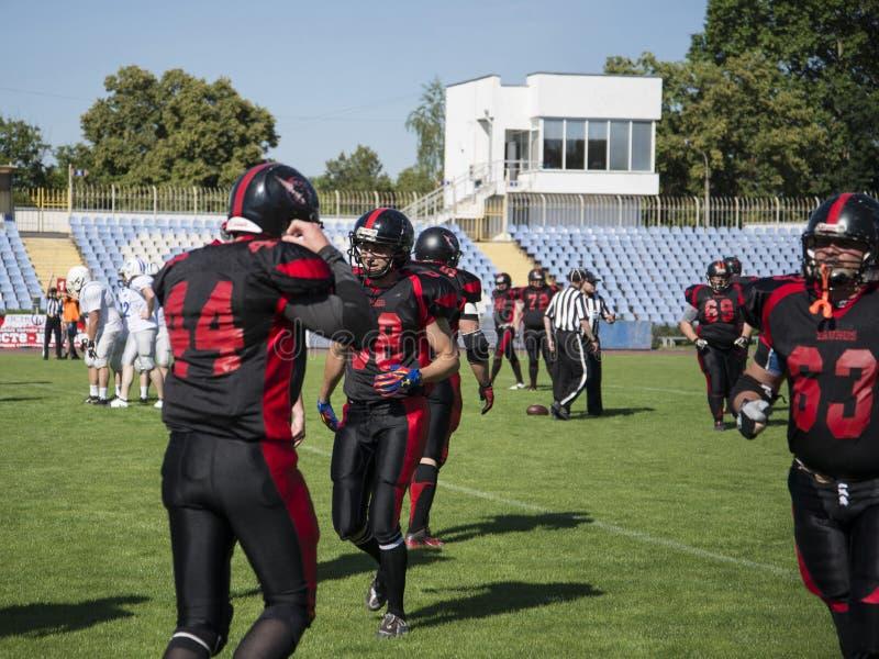 Teams für amerikanischen Fußball gegen den Hintergrund eines grünen Feldes stockfotografie