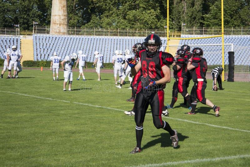 Teams für amerikanischen Fußball gegen den Hintergrund eines grünen Feldes stockbild