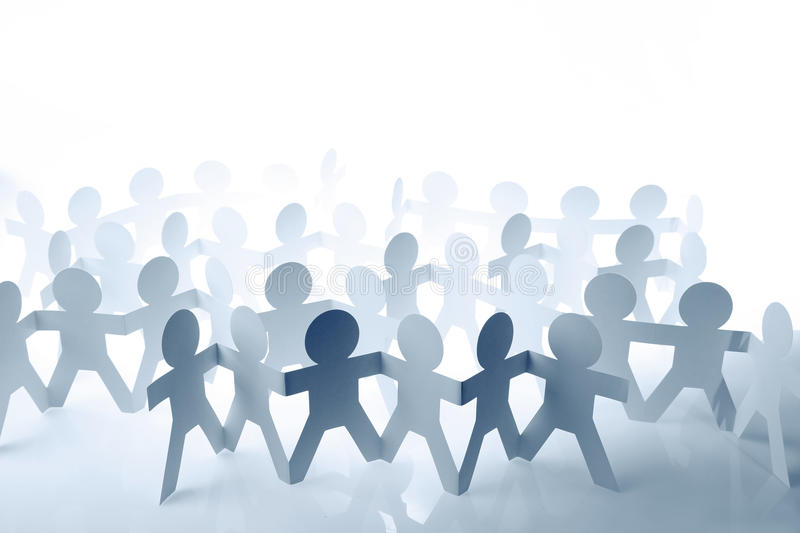 Teams. Of paper doll people holding hands stock photo