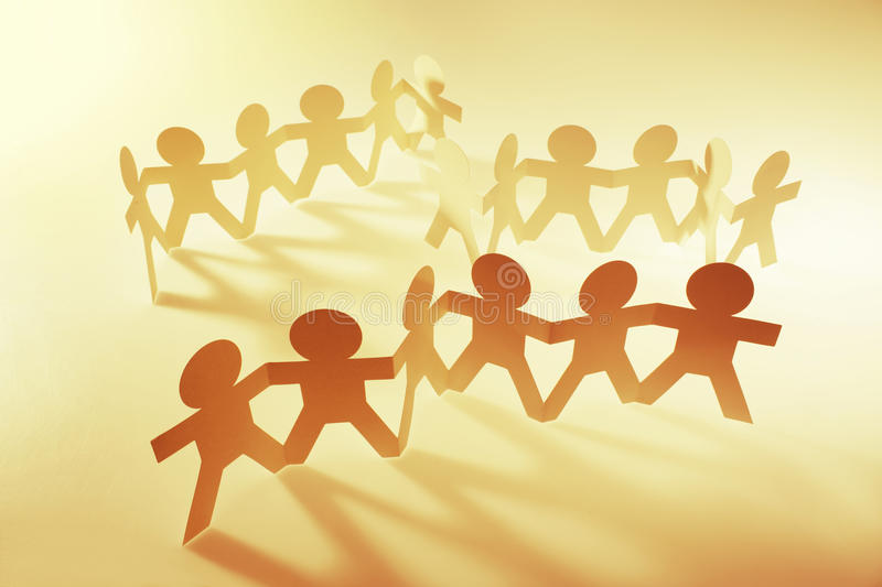 Teams united together. Paper chain people teams holding hands royalty free stock photos