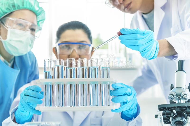 Teamwetenschapper die in laboratorium werken Reageerbuizen met vloeistof in laboratorium, de holdingsdruppelbuisje van de Artsenh stock afbeeldingen