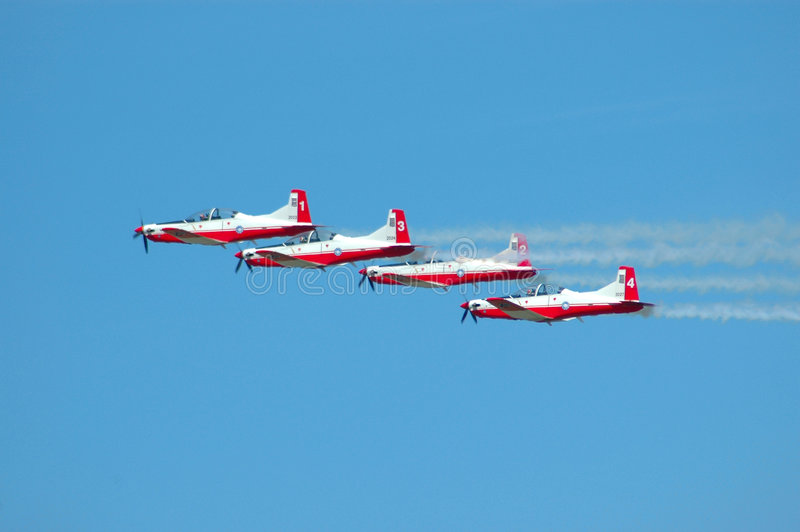 Teamwork. Four colorful airplanes in red and white flying in the air on a flight air show showing a flight formation stock photo