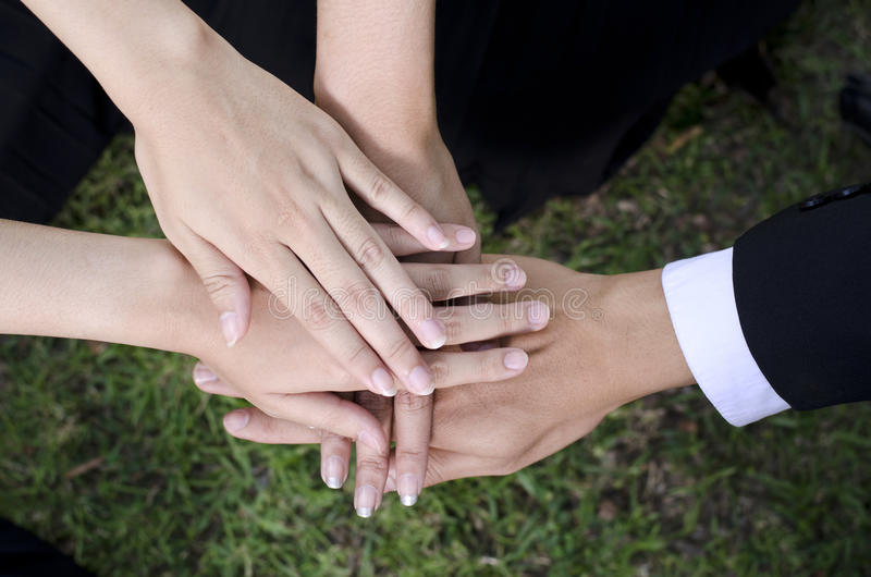 Teamwork. People putting their hands on top of each other stock image