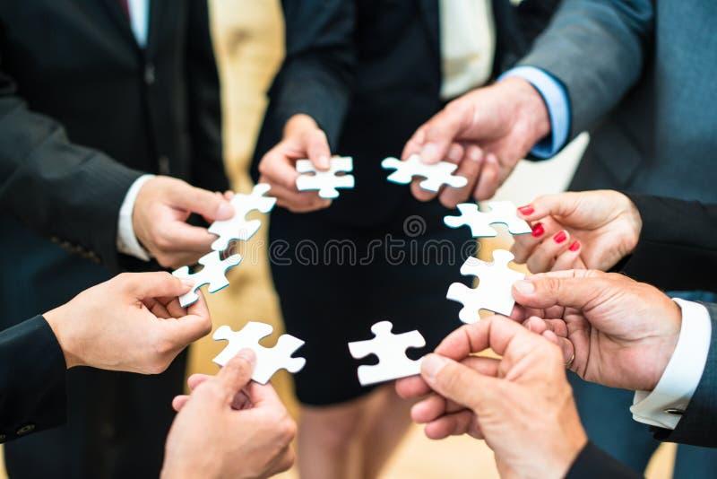 Teamwork - affärsfolk som löser ett pussel arkivbild