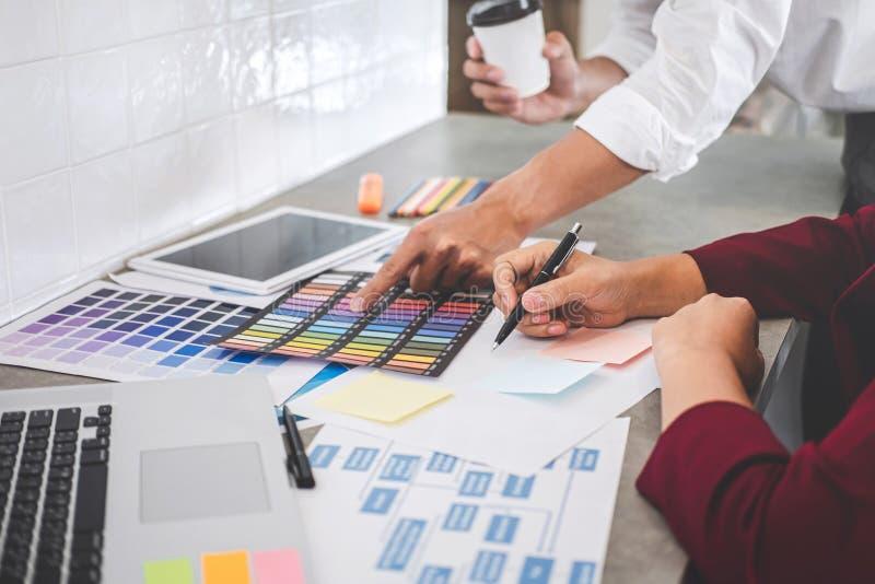 Teamwork av unga id?rika formgivare som tillsammans arbetar p? projekt och att v?lja f?rgprovkartapr?vkopior f?r valf?rgl?ggning  arkivbild