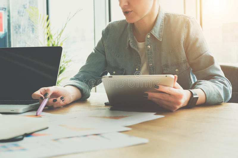 Teamwork, brainstorming. Businesswoman sitting at table and holds tablet computer while showing pen on charts on table. On desk laptop and notebook and paper royalty free stock images