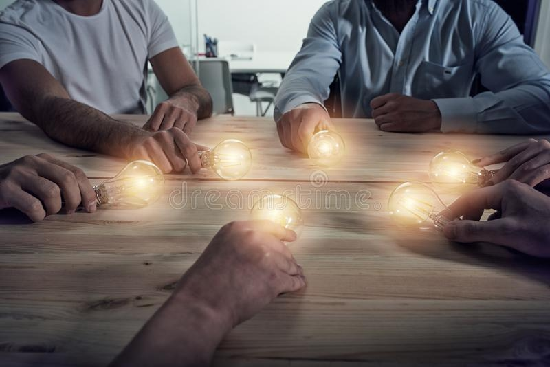 Teamwork and brainstorming concept with businessmen that share an idea with a lamp. Concept of startup. Teamwork and brainstorming concept with businessmen that stock image