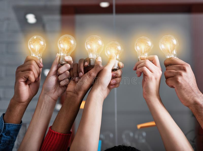 Teamwork and brainstorming concept with businessmen that share an idea with a lamp. Concept of startup. Teamwork and brainstorming concept with businessmen that royalty free stock photo