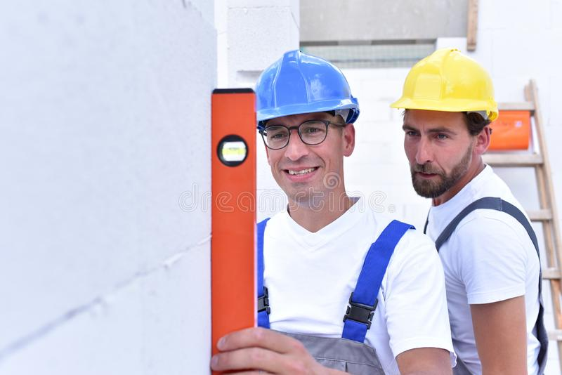 Teamwork on the building site - construction workers build a family home royalty free stock photos