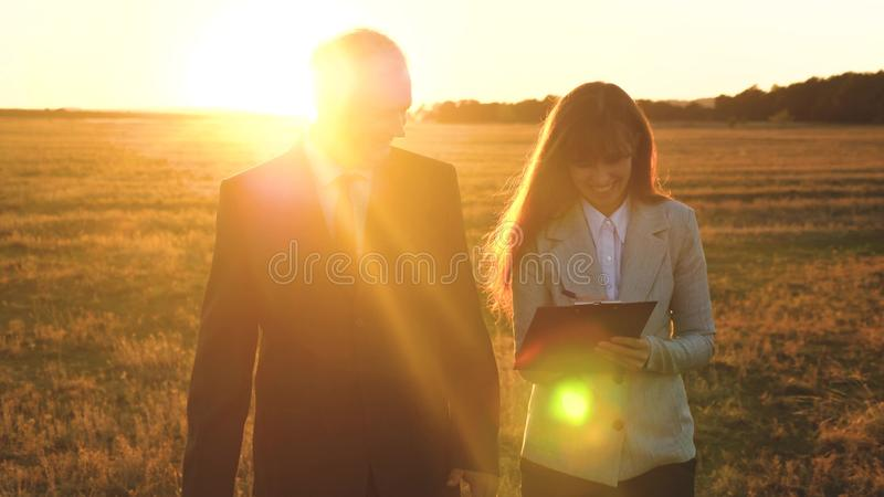 Teamwork of business people.businessman and businesswoman discuss teamwork plan in the park at sunset. team of business. Teamwork of business people.businessman royalty free stock photo