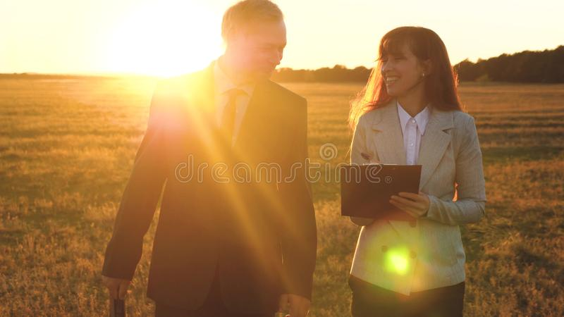 Teamwork of business people.businessman and businesswoman discuss teamwork plan in the park at sunset. team of business. Teamwork of business people.businessman stock image