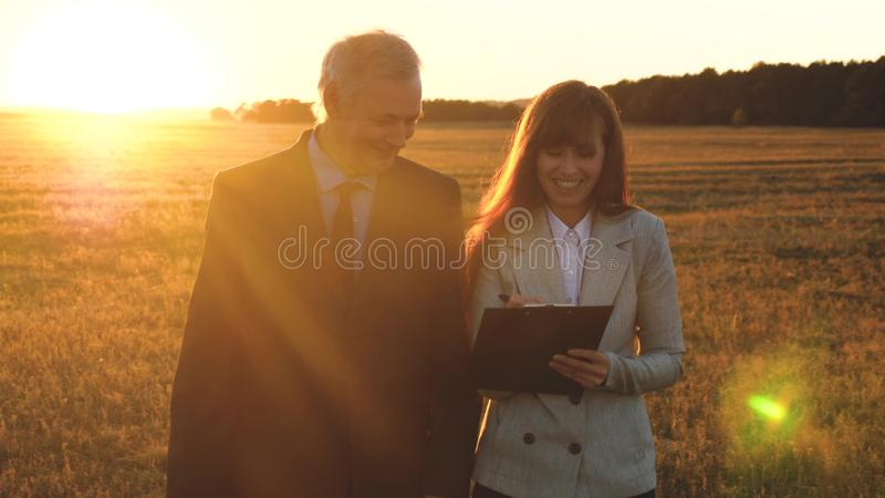 Teamwork of business people.businessman and businesswoman discuss teamwork plan in the park at sunset. team of business. Teamwork of business people.businessman royalty free stock photography