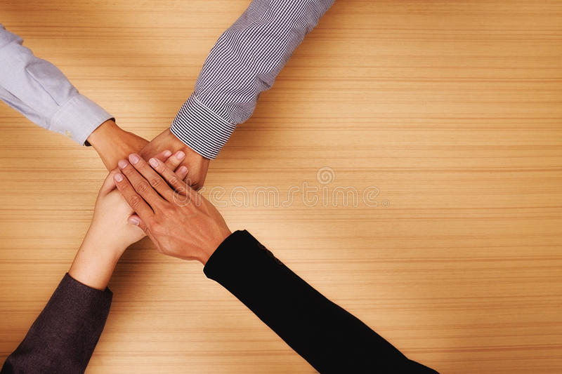 Teamwork,Business team standing hands together in the office royalty free stock photography