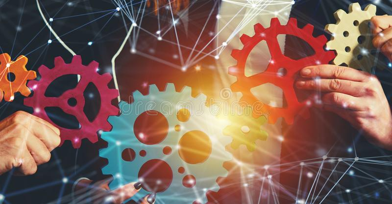 Business team connect pieces of gears. Teamwork, partnership and integration concept with network effect stock image