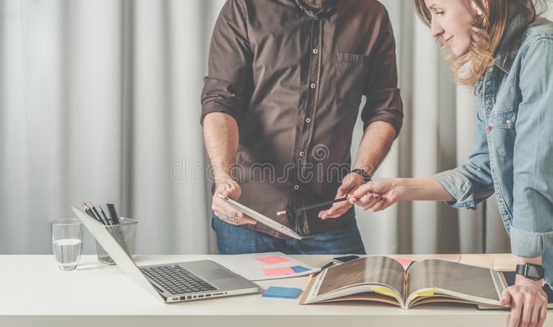 Teamwork businesswoman standing and shows pencil on screen tablet computer in hands of businessman. royalty free stock photos