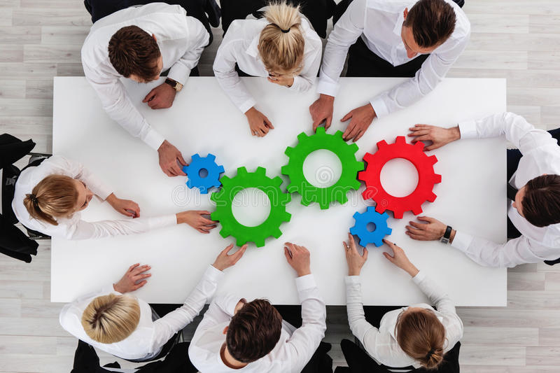 Teamwork with cogs of business. Business team sitting around the table with cogs, teamwork concept royalty free stock photos