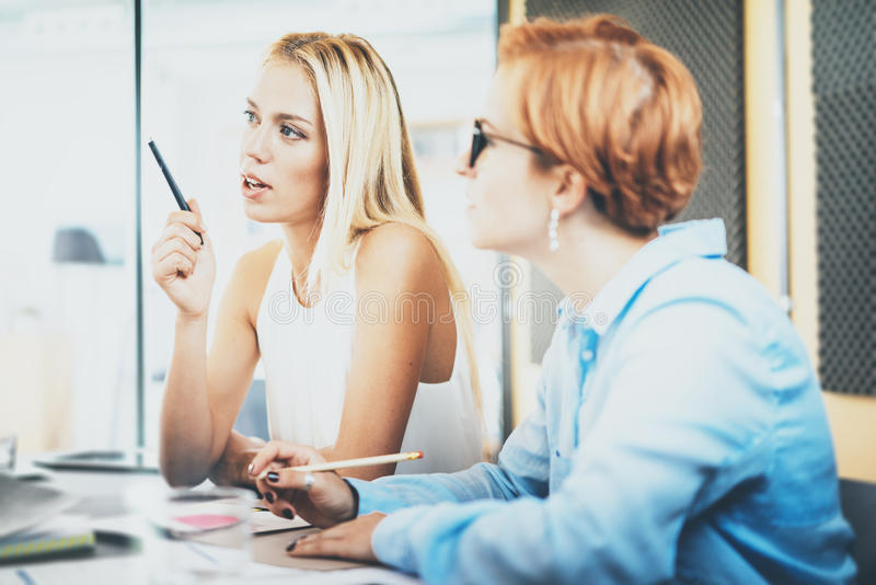 Teamwork concept of beautiful womans making business meeting in modern office. Group girls coworkers discussing together. New project. Horizontal, blurred royalty free stock photography