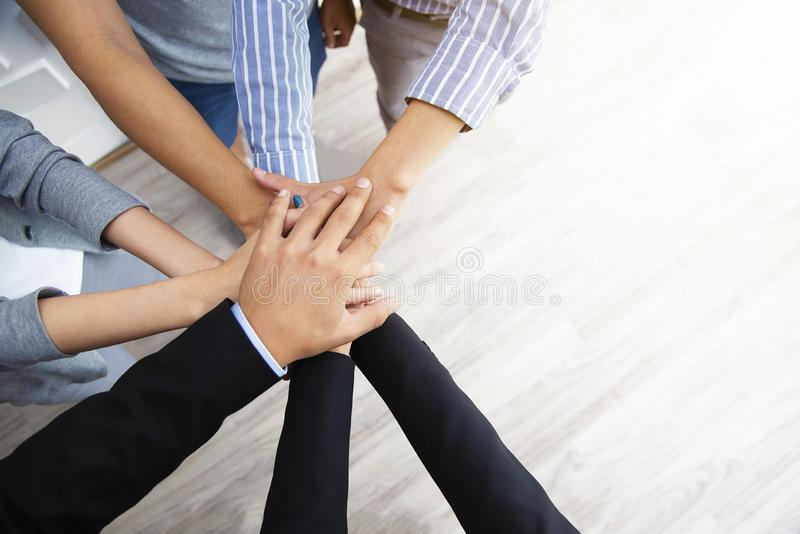 Teamwork concept. Business peoples putting their hands together. In top view. Stack of hands for unity and team. Success business stock images