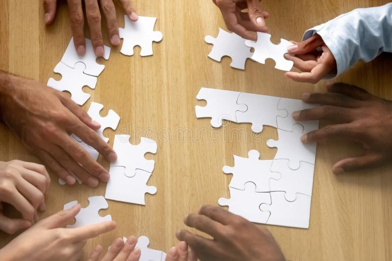 Teamwork concept, business team people hands assemble puzzle together. Teamwork concept, multi ethnic business team people hands assemble puzzle together engaged stock photos