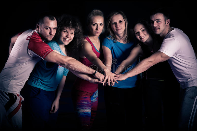 Teamwork concept.Fitness workout team motivation.Group of athletic healthy adults in gym giving group high five.United hands. stock photo