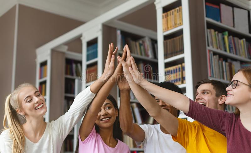 Students putting their hands up together in library. Teamwork concept. Group of happy students putting their hands up together in library, free space stock photography