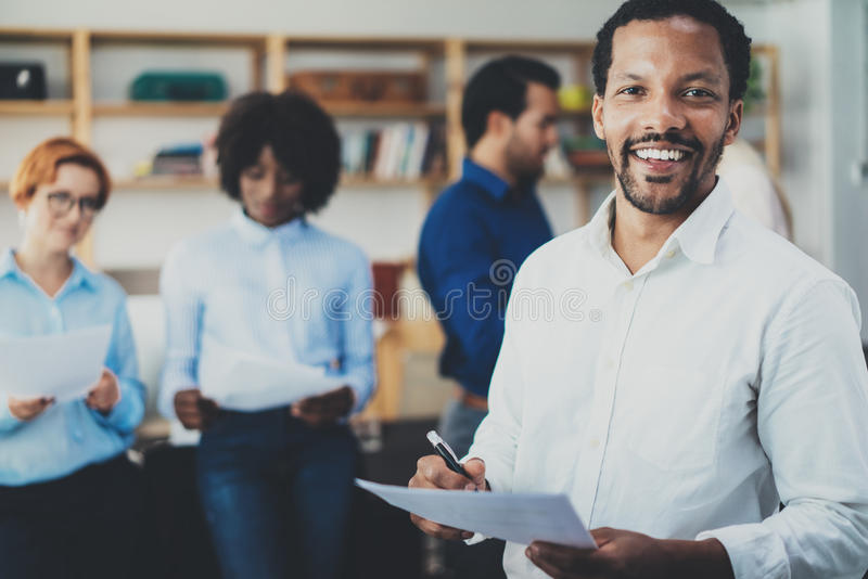 Teamwork concept in modern office.Young african businessman wearing white shirt holding papers at hands and standing stock images