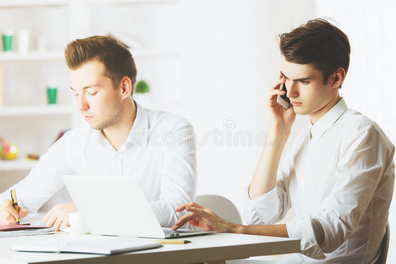 Teamwork concept. Portrait of handsome european gentlemen at workplace working on project and talking on mobile phone. Teamwork concept royalty free stock photography